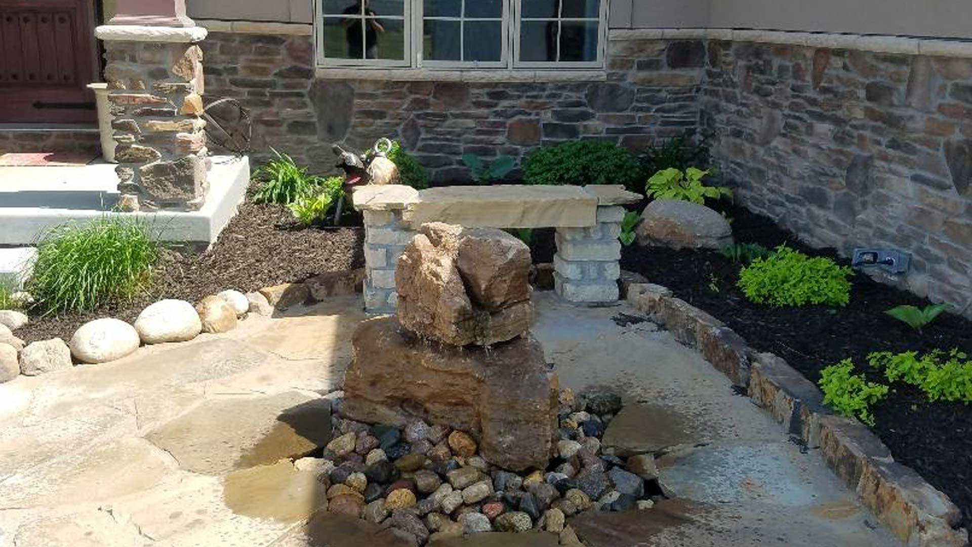 Landscaping installed in front of a home in Lincoln with a water feature as a focus.