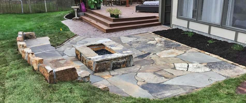 Custom square flagstone fire pit with a flagstone patio and seating wall at a home in Lancaster County.