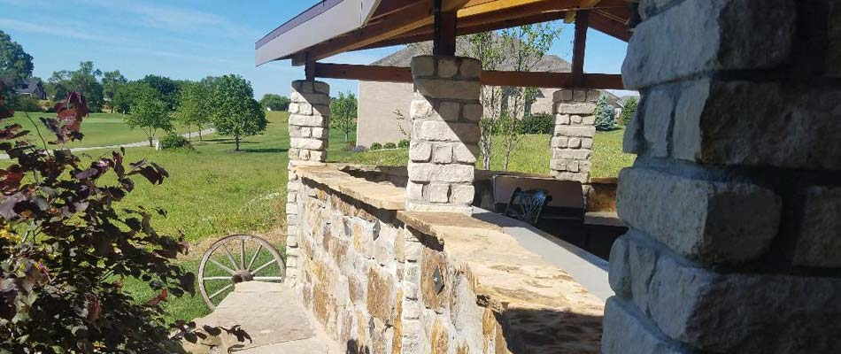 Outdoor living space with a kitchen, seating area and pergola at a home in Lincoln, NE.